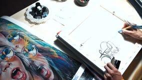De meisjeskunstenaar ondertekent sommige van zijn werken Geschilderd teken van een meester Canvas op een zwarte teller van de bra stock video