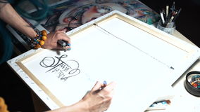 De meisjeskunstenaar ondertekent sommige van zijn werken Geschilderd teken van een meester Canvas op een zwarte teller van de bra stock videobeelden
