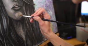 De meisjeskunstenaar schildert een beeldmedicijnman De kunstenaar schildert beeld op canvas met acrylverven in haar workshop stock footage