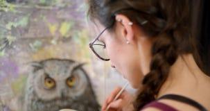 De meisjeskunstenaar schildert een beeldmedicijnman De kunstenaar schildert beeld op canvas met acrylverven in haar workshop stock videobeelden