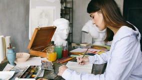 de meisjeskunstenaar trekt schetsen op de Desktop Zachte nadruk over van het venster De workshop wordt gevuld met het klassieke G stock footage