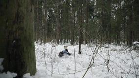 De meisjeslooppas door het de winterbos en gestruikeld in de sneeuw stock video