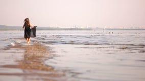 De meisjeslooppas langs de kustlijn op de achtergrond van de stad en doet schrikken de zeemeeuwen stock footage