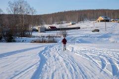 De meisjeslooppas weg over het bevroren meer in de richting van het dorp op een heuvel, op een de winter zonnige dag royalty-vrije stock fotografie