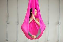 De meisjeslotusbloem stelt lucht antigravity yoga De vrouw zit in hangmat Royalty-vrije Stock Fotografie