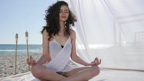 De meisjesmeditatie, in bungalow, wijfje met krullen, op achtergrondoverzees en zand, wind ontwikkelt haar en witte doek,  stock videobeelden