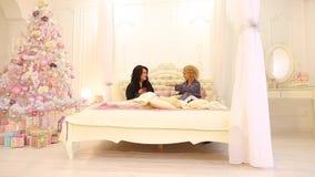De meisjesmeisjes communiceren bij pyjamapartij en hebben pret samen, zittend op bed in heldere slaapkamer laat bij nacht stock videobeelden