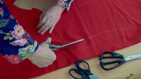 De meisjesnaaister verwijdert detail voor kleren met schaar stock videobeelden