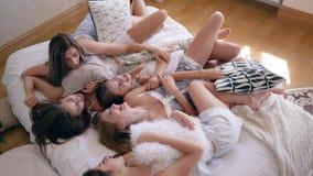De meisjespartij, gelukkige vrienden in pyjama's heeft pret die met hoofdkussens op bed liggen stock footage