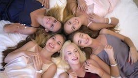 De meisjespartij, portret van gelukkige blije mooie meisjes in pyjama's die op bed liggen heeft pret thuis babbelend partij in stock video