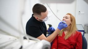 De meisjespatiënt bij tandartskabinet maakt tot mondelinge hygiëne tandbehandeling tijdens chirurgie stock footage