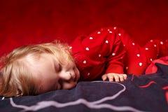 De meisjespeuter kleedde zich in haar pyjama's het slapen Stock Fotografie