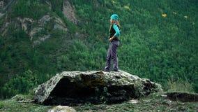 De meisjesreiziger in een vest en een hoed bevindt zich op een grote steen in de boom-behandelde bergen stock videobeelden
