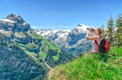 De meisjesreiziger kijkt door verrekijkers, tegen een achtergrond van mo royalty-vrije stock afbeelding