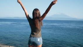 De meisjesreiziger spreidt haar wapens uit wijd, geniet van mening van oceaan, bergen, langzame motie stock footage
