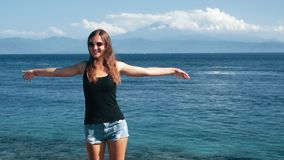 De meisjesreiziger spreidt haar wapens uit wijd, geniet van reis en vakantie, langzame motie stock video