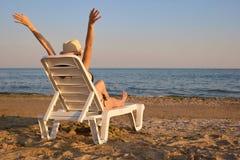De meisjesrust op sunbed op de kust Royalty-vrije Stock Afbeelding