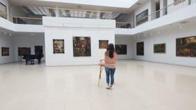 De meisjesschilder bevindt zich in het centrum van de galerij vóór het witte canvas op de schildersezel 4K stock video