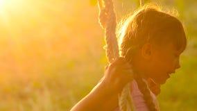 De meisjesschokken op een schommeling op een zonsondergang stock footage