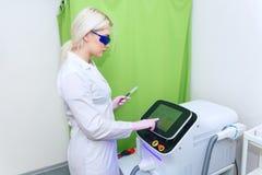 De meisjesschoonheidsspecialist met blond haar past het apparaat haarverwijdering met aan een laser Kosmetisch materiaalapparaat stock fotografie
