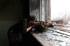 De meisjessluipschutter kijkt door het werkingsgebied De meisjesstrijder leidt zijn geweer door het gebroken venster van een verl stock afbeelding