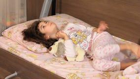 De meisjesspelen ongeveer in een bed Doesn ` t wil slapen stock videobeelden