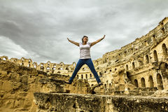 De meisjessprong schoot tegen de achtergrond van Roman amphitheatr Stock Afbeelding