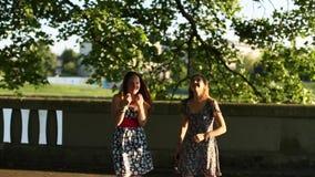 De meisjessprong van tienermeisjes in het Park onder een boom stock footage