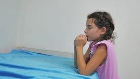 De meisjestiener bidt vóór bedtijd het knielen door het bed van een meisje en het bidden van de godsdienst van geloof stock video