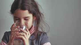 De meisjestiener drinkt water van een glaskop binnen royalty-vrije stock afbeeldingen