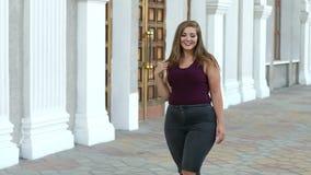 De meisjestiener met bovenmatig gewicht in gescheurde jeans gaat rond de stad stock footage
