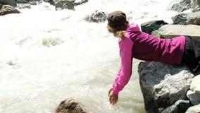 De meisjestoerist drinkt water met behulp van handen van een bergrivier stock footage
