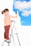 De meisjestribune van vier jaar op een ladder en trekt een pictu stock afbeeldingen
