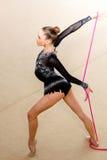 De meisjesturner presteert met een kabel bij de concurrentie stock afbeeldingen