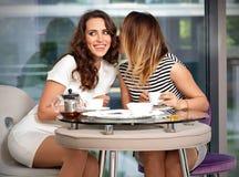 De meisjesvrienden in koffie roddelen stock fotografie