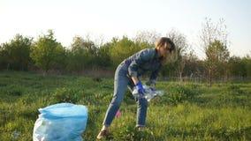 De meisjesvrijwilliger verzamelt plastic afval in het park Zonsondergang en winderig weer stock footage