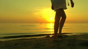 De meisjesvrouw loopt langs een zandig overzees strand blootvoets op een zonsondergangachtergrond Het meisje loopt in langzame mo stock footage