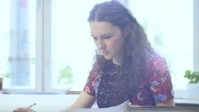 De meisjeswerken met documenten die tegenover computer zitten stock footage