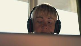 De meisjeszakenman in hoofdtelefoons communiceert op Internet in de stralen van de zon stock videobeelden
