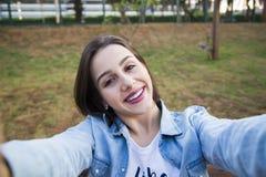 De meisjeszitting in het park en maakt selfie, gelukkig royalty-vrije stock foto