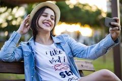 De meisjeszitting in het park en maakt selfie, gelukkig stock afbeeldingen