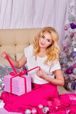De meisjeszitting op de laag en pakt Kerstmisgiften uit Royalty-vrije Stock Foto's