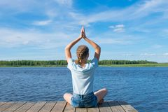 De meisjeszitting op de pijler, die zijn handen opheffen omhoog, nam in meditatie in dienst, tegen het meer stock foto's