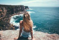 De meisjeszitting op rotsen en het enjoing van de oceaan stock fotografie