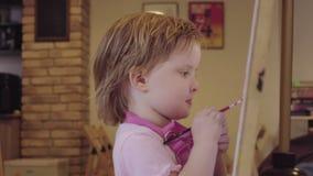 De meisjeverven op een canvas die, die en ter goedkeuring weggaan wachten stock video
