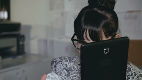De meisjewerken met PC en tablet in bureau 4K stock footage