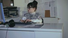 De meisjewerken met PC en tablet in bureau 4K stock videobeelden