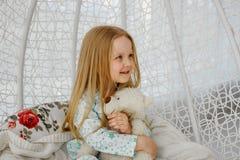 De meisjezitting als voorzitter schortte cocon of in een schommelstoel in een helder binnenland op De zitting van het meisje als  stock afbeeldingen