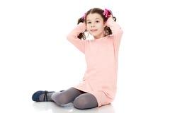 De meisjezitting op de vloer en maakt haar recht Stock Afbeelding