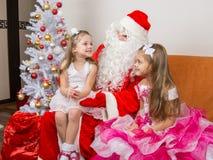 De meisjezitting op overlapping van Santa Claus en vertelt gedicht royalty-vrije stock fotografie